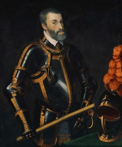 A portrait of Charles V, wearing black and gold armor and posed with his helmet in the foreground.